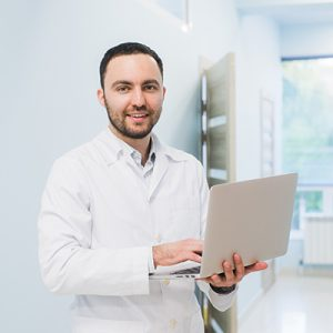 Portrait Of Doctor Holding Laptop, Indoors at hospital